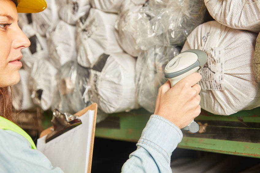 Woman with checklist and scanner in warehouse