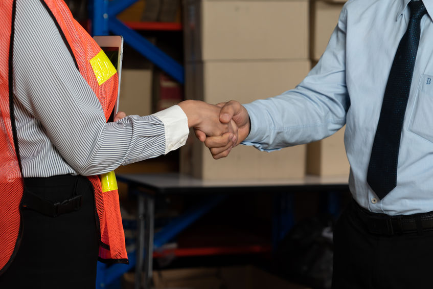 Warehouse worker shaking hands with client